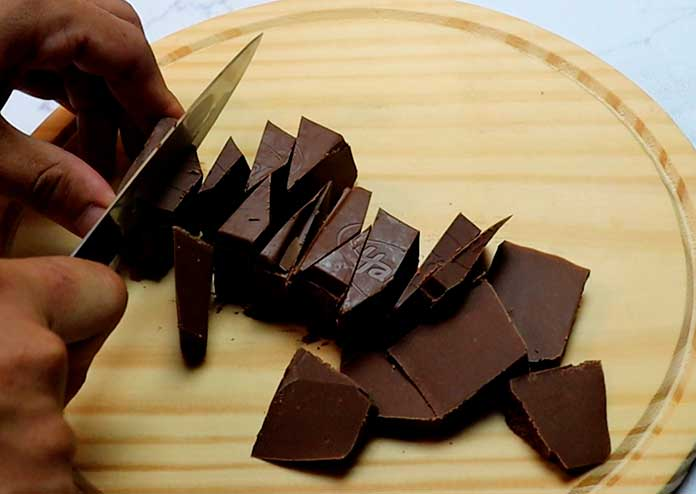 Para preparar a mousse comece cortando o chocolate